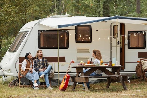 森のコピースペースでバンとキャンプしながらアウトドアを楽しんでいる友人の広角ビュー