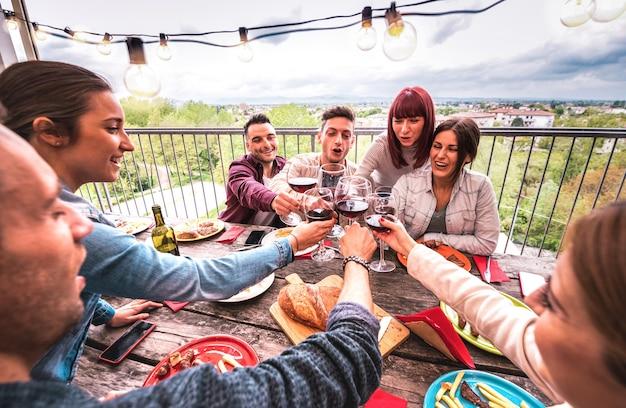 야외 빌라의 옥상 파티에서 레드 와인을 함께 토스트하는 행복한 사람들의 넓은 각도 보기