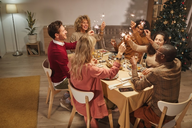 Широкий угол обзора людей, жарящих с бокалами шампанского, наслаждаясь рождественским ужином с друзьями и семьей и держа в руках бенгальские огни.