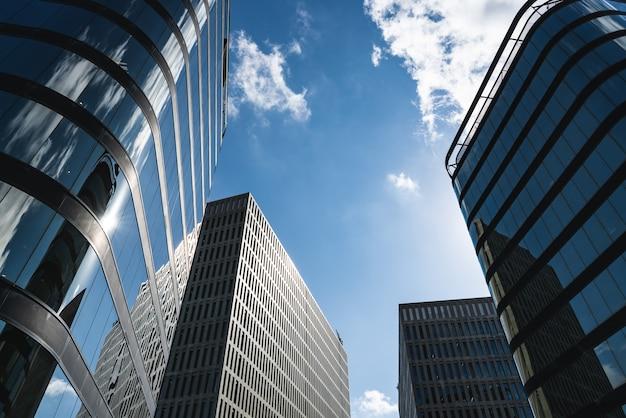 Широкий угол обзора нескольких офисных зданий с застекленными и бетонными фасадами.