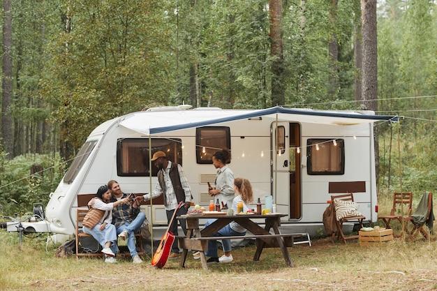 森のコピースペースでバンとキャンプしながらアウトドアを楽しむ若者の広角ビュー