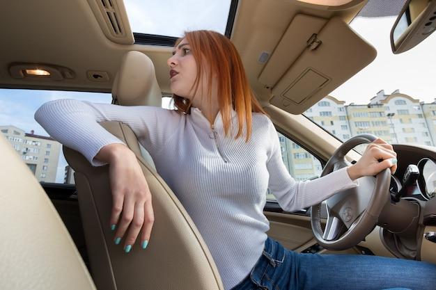 뒤를 돌아보며 차를 몰고 있는 젊은 빨간 머리 여성 드라이버의 광각 보기.