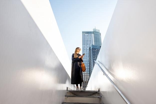 近代的な街の階段を歩いている女性と白い橋の広角ビュー