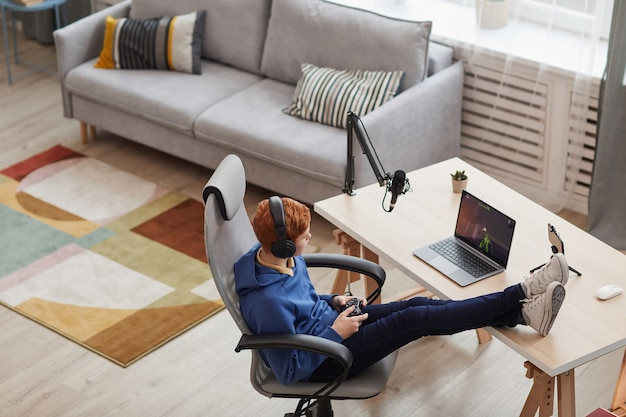 Wide angle above view at red haired teenage boy playing video games via laptop while relaxing in designer room, copy space