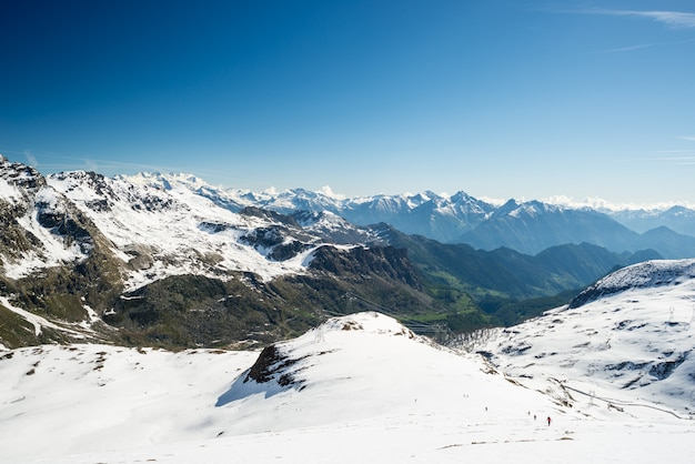 Wide angle view of a ski resort in the distance with elegant mountain peaks arising