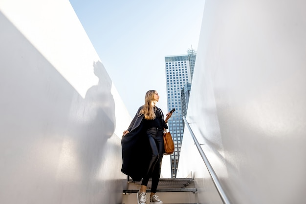 Wide angle view on the white bridge with woman walking down the stairs at the modern city