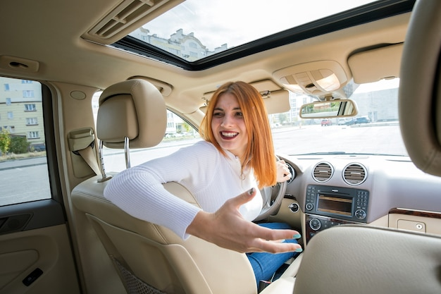Wide angle view of young redhead woman driver driving a car backwards looking behind.