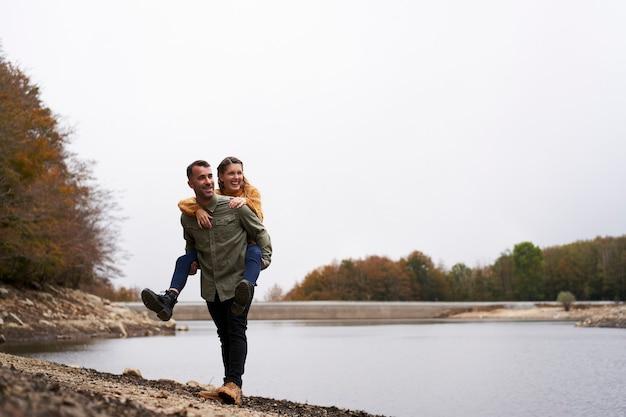 Широкоугольный молодой человек в любви, спрятав свою девушку у озера
