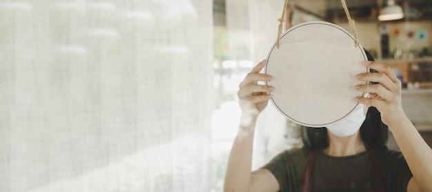 広いバナー。カフェレストラン、広告、広告マーケティング、中小企業の所有者の概念のガラスのドアにぶら下がっている空白の木製看板を回す保護フェイスマスクを身に着けているウェイトレススタッフ
