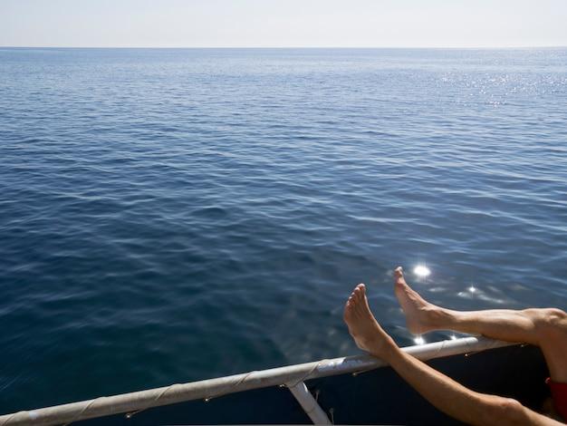 편안한 포즈로 알 수없는 인간의 다리가있는 선상의 조각이있는 넓은 푸른 바다