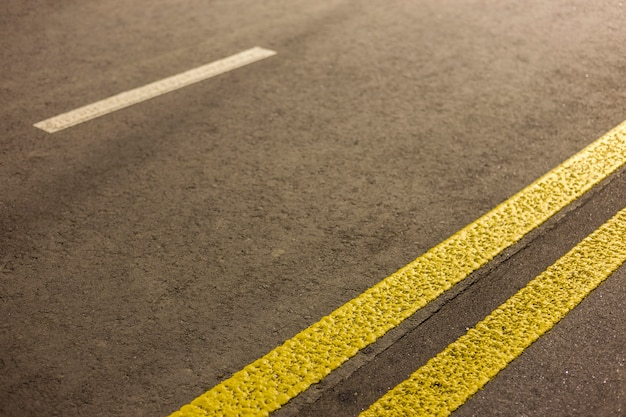 Wide bright double yellow marking sign line along modern wide smooth empty asphalt highway street stretching to horizon. speed, safety, comfortable journey and professional road building concept.