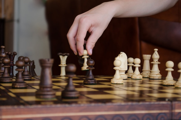 Wide cropped image of a human hand moving a chess piece of a light pawn