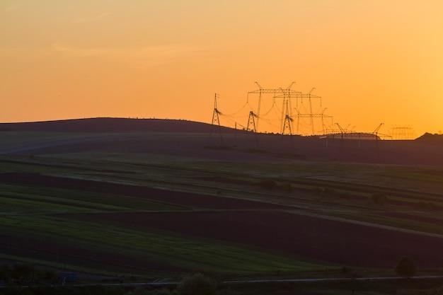 어두운 보았다고 및 녹색 필드와 석양 아름 다운 밝은 노란색 오렌지 하늘에 수평선을 스트레칭하는 전력선의 넓은 저녁 파노라마 자연, 농업 및 농업 개념의 아름다움입니다.
