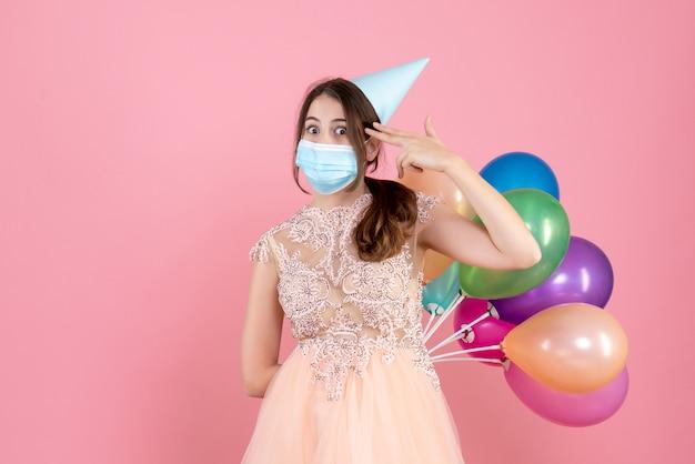 분홍색 사원 근처에 손가락 총을 유지하는 그녀의 뒤에 다채로운 풍선을 들고 파티 모자와 넓은 눈동자 소녀