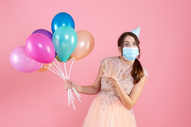 Ragazza con gli occhi spalancati con tappo del partito che tiene palloncini colorati sul rosa