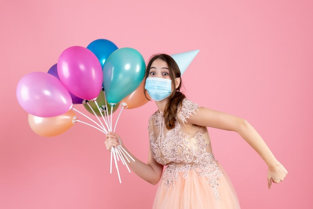ピンクにカラフルな風船を持って走っているパーティーキャップを持つ目を丸くした女の子