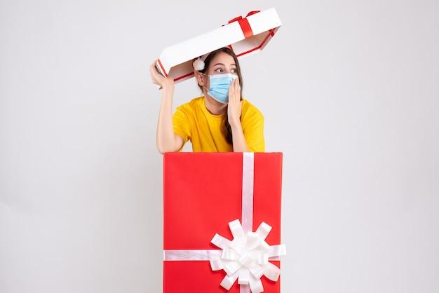 白の大きなクリスマスプレゼントに立っているサンタの帽子と目を丸くした女の子