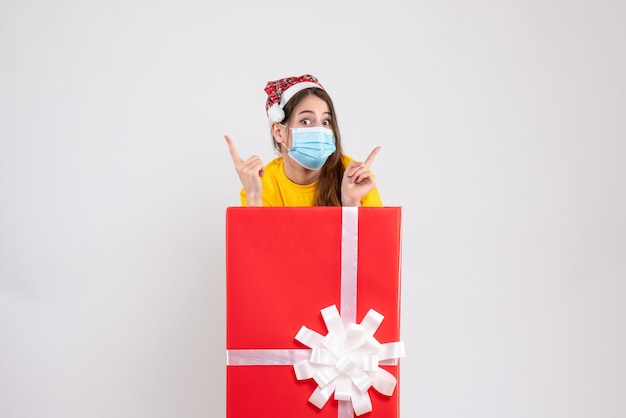 Wide-eyed xmas girl with santa hat pointing at something standing behind big xmas gift on white