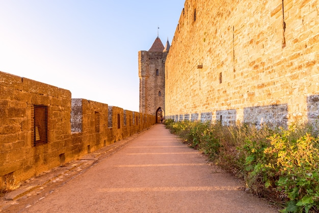 日没時のカルカソンヌの町の中世の城の通路とアーチのある広い要塞の壁