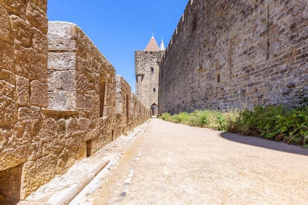 カルカソンヌの町の中世の城の通路とアーチのある広い要塞の壁