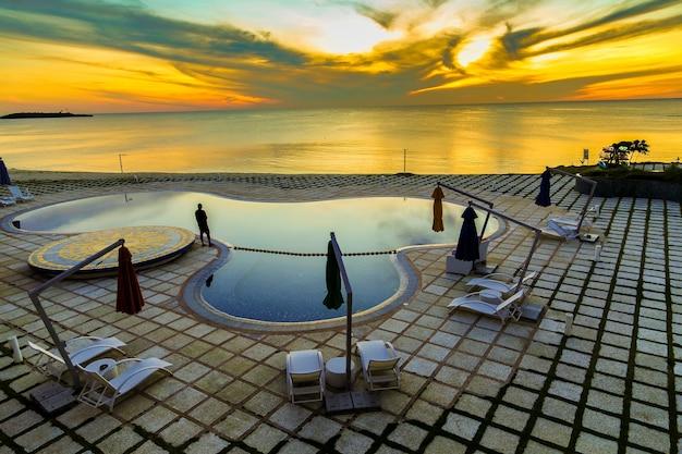 Широкоугольный снимок частного бассейна на фоне океана в час заката