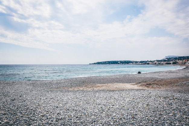Wide landscape shot of a pebbly seashore by the sea under a clear sky