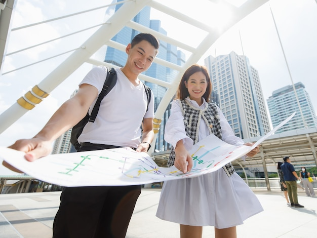 Wide-low angle view portrait of smiling young happy lover an asian travelers standing and looking paper metro map together with woman pointing map to find target station with blurred map foreground