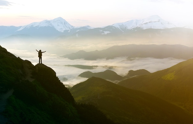 넓은 산 파노라마입니다. 하얀 푹신한 구름으로 덮인 계곡 위로 손을 들고 바위산 경사면에 배낭을 메고 있는 관광객의 작은 실루엣. 자연의 아름다움, 관광 및 여행 개념