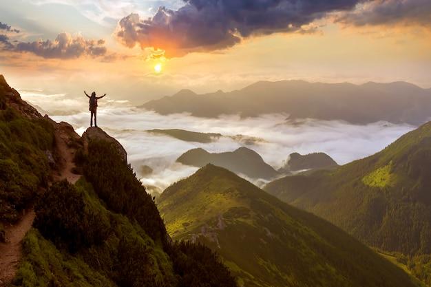 Широкая горная панорама. маленький силуэт туриста с рюкзаком на скалистом склоне горы с поднятыми руками над долиной, покрытой белыми тучными облаками. красота природы, туризм и концепция путешествий