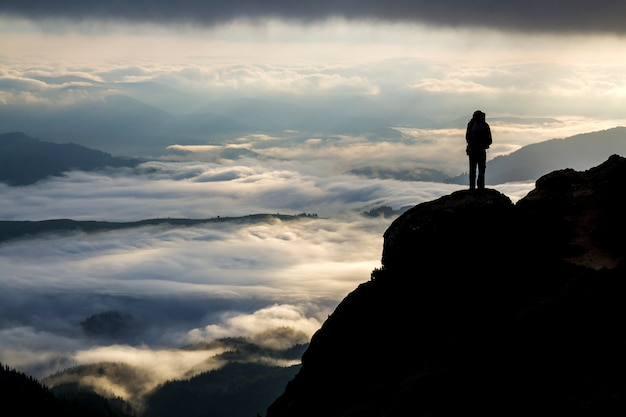 Wide mountain panorama. small silhouette of tourist with backpack on rocky mountain slope over valley covered with white puffy clouds. beauty of nature, tourism and traveling concept