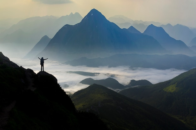 Wide mountain panorama. small silhouette of tourist with backpack on rocky mountain.