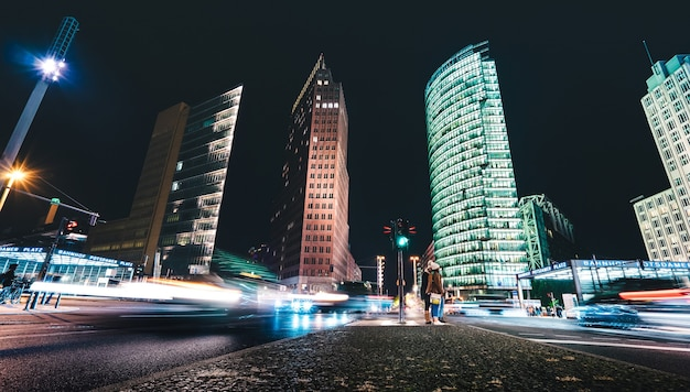 Wide nightscape of potsdamer platz with unrecognizable people and blurred traffic jam