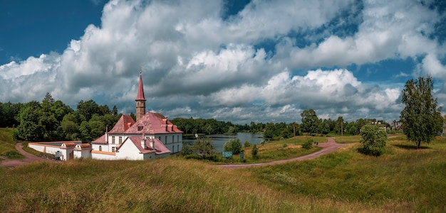 A wide panorama of the beautiful natural landscape. old castle, blue sky and white fluffy clouds at the sunny summer day. gatchina. russia.