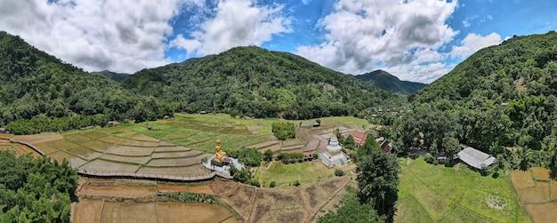 タイ、プレーの旅行先であるワットナクハまたはナクハ寺院の緑米の山にある黄金の仏像と白い塔の広いパノラマの高角度ビュー
