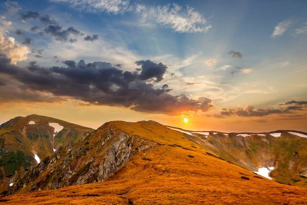 Wide panorama of lit by sun yellow rocky mountain ridge with patches of snow in valleys stretching to horizon under bright blue cloudy sky background. beauty of nature, tourism and traveling concept.