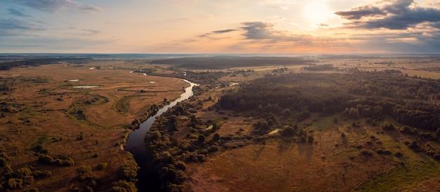Широкая панорама небольшой речки в сельской местности утром на фоне восходящего солнца