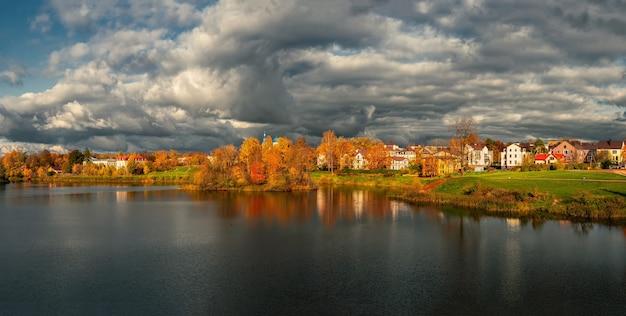 湖のほとりにコテージと黄色の木々がある劇的な田園地帯の広いパノラマ。