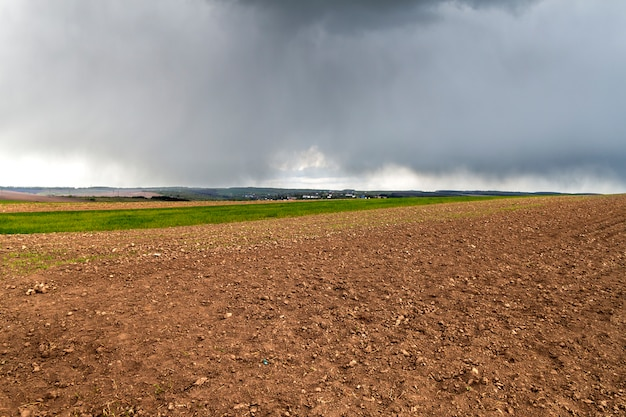 Wide panorama of plowed empty field before planting stretching to woody hills and distant village on horizon under dramatic cloudy dark sky. summer or spring landscape, agriculture and farming.