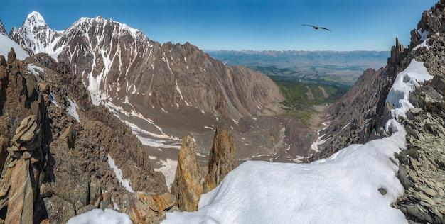 雪をかぶった山頂と青い空の下の鋭い岩のある広いパノラマの高山の風景。雪山の頂上とカラフルな日当たりの良い山の風景。