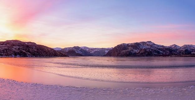 피요르드 위에 놀라운 마젠타 색상으로 겨울 일몰의 넓은 파노라마 뷰