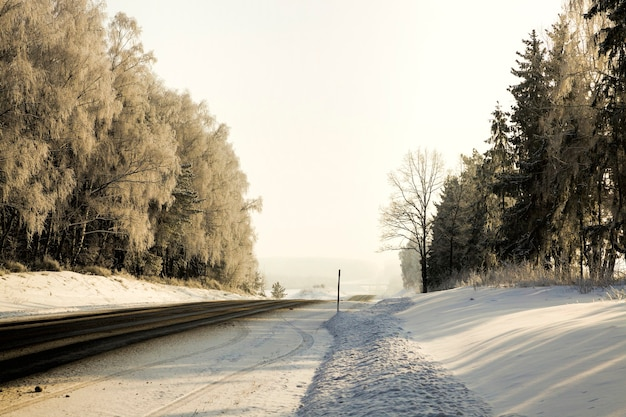Широкая асфальтированная зимняя дорога, покрытая снегом после зимних снегопадов, опасный и трудный участок пути в морозную зимнюю погоду.