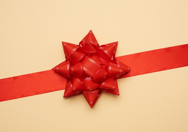 Wide red silk ribbon and big bow on beige background, gift wrap, top view