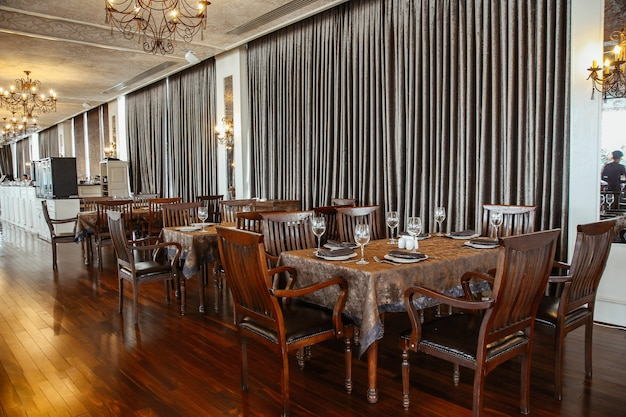 Wide restaurant hall with wooden table and chairs for 6 persons