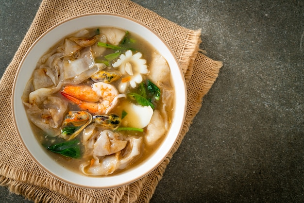 Wide rice noodles with seafood in gravy sauce - asian food style