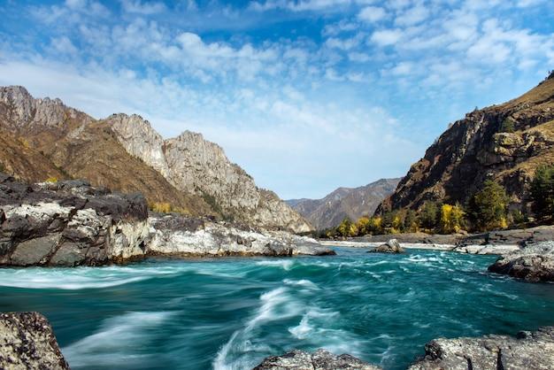 広い川は澄んだ青い空を背景に岩が多い山の間の石の多い銀行に沿って流れます。荒れ模様の川と巨大な石の青緑色の水。