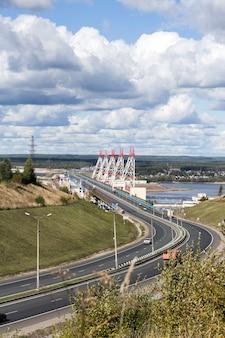 ヴォルガ川の大きな川の水力発電所を横切る橋の広い道路。