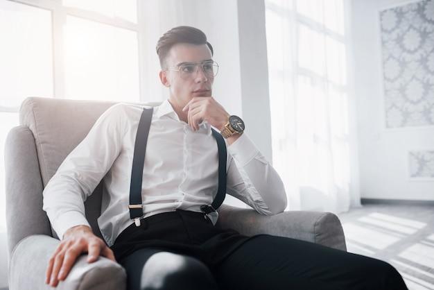 넓은 방. 손에 멋진 시계. 안경에 매력적인 남자의 사진과 의자에 앉아 세련된 착용을 닫습니다.