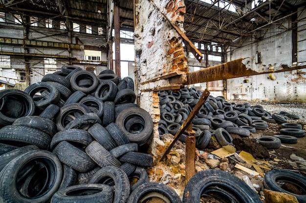 Широкое резиновое колесо от автомобиля, лежащего на фоне изношенных шин с легкими протечками на старом заводе. изношенные шины на земле в заброшенном разрушенном заводе в помещении