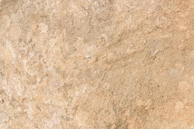 デザインの広い砂浜の赤みを帯びた石のテクスチャ背景
