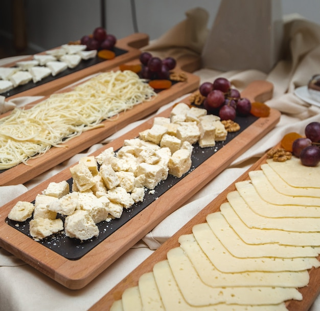 A wide selection of cheese platters with fresh grapes on the table.